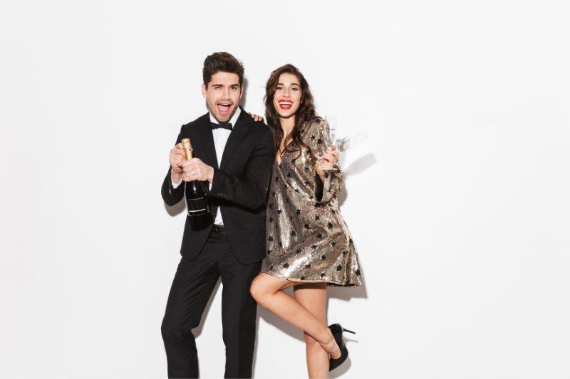 jeune couple ouvrant une bouteille de champagne pour le jour de l'an